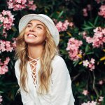 Outfit Tips To Help You Stay Cool & Look Fabulous- smiling woman in white hat and flowy summer top