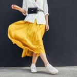 A stylish woman wears a bright yellow skirt with a casual white top and white runners that's perfect for a spring day.